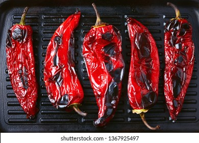 Close-Up Of Roasted Red Peppers On Grilling Pan.