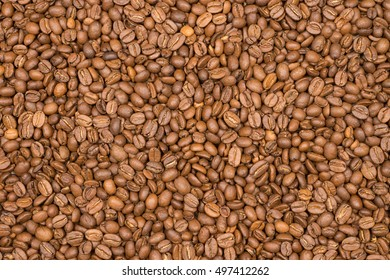 Close-up of roasted spilled coffee beans background