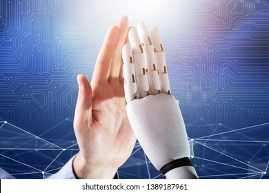 Close-up Of Robot And Man Giving High Five Against Digital Background