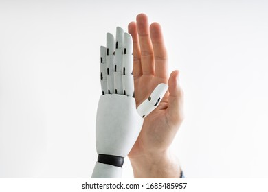 Close-up Of Robot And Man Giving High Five Against Gray Background