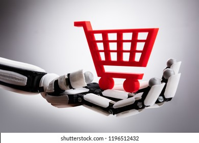 Close-up Of A Robotic Hand Holding Red Shopping Cart On Gray Background