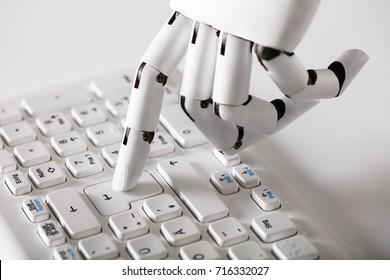Close-up Of Robotic Hand Pressing Enter Key On Keyboard