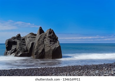 Close-up of rock formation at the coastline against blue sky. Praia Formosa beach in Funchal on Portuguese island of Madeira