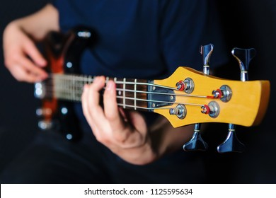 Closeup of rock guitarist practicing with bass guitar.