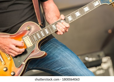 closeup of a rock musician strumming an electric guitar