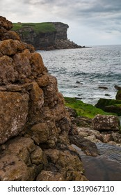 Close-up of rocks in a cliff landscape. A cloudy summer day on the coast of Cantabria. Spain