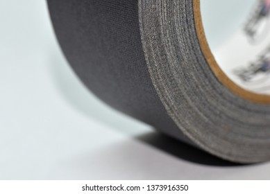 Closeup of a roll of black gaffer tape on light blue background, side view.