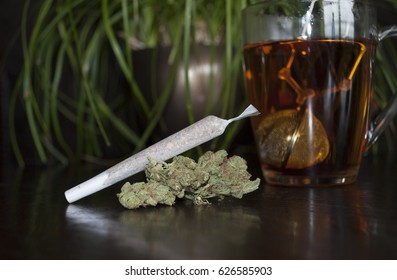 closeup of rolled marijuana weed, Cannabis Sativa, joint and buds on wooden background, with cup of rooibos tea