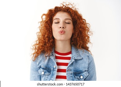 Close-up romantic cute feminine silly redhead girl curly hairstyle prepared lips kiss folding mouth close eyes wanna receive muah standing white background express love tenderness and sympathy