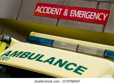 A close-up of the roof of an NHS ambulance showing Ambulance signage and light bar with an Accident and Emergency sign directly above - all tilted to the right