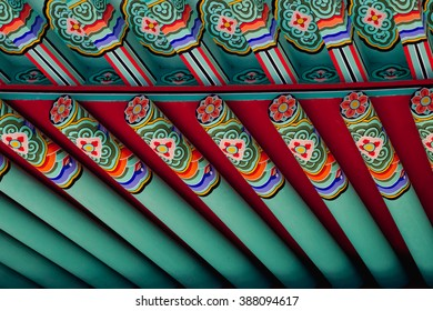 Closeup of the Roof of a South Korean Buddhist Temple with Teal, Red, and Green Pattern Wooden Beams