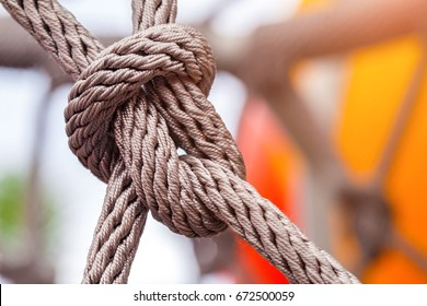 Close-up of rope knot line tied together with playground background