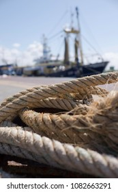 Close-up of the ropes of a trawl fishing gear on the quay of a harbor with blurry fishing boat at background