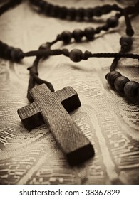 closeup of rosary cross,shallow DOF with focus on the cross, light sepia toned with vignette