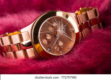 Closeup the rose gold wrist watch with cracked glass. The broken wrist watch. Concept of crime and accident.