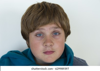 Closeup of round faced pre-teen boy with wide-open eyes looking surprised