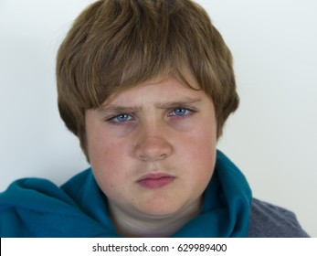 Closeup of round faced pre-teen boy looking angry