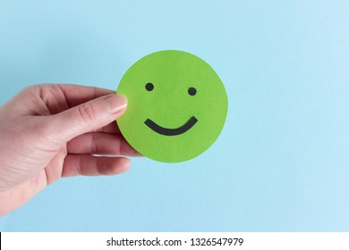 Closeup of round happy smiley of green color in crop hand against blue background