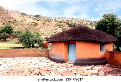 Close-up round hut rondavel. Basotho tribe village. South Africa. Clay house with the straw roof. Exterior of the ethnic rural building. Retro local architecture. Drakensberg mountains background.