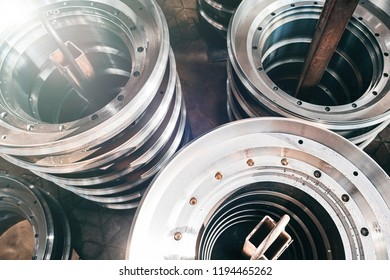 Closeup of round metal flanges for valve manufacture in a factory. Industrial background.