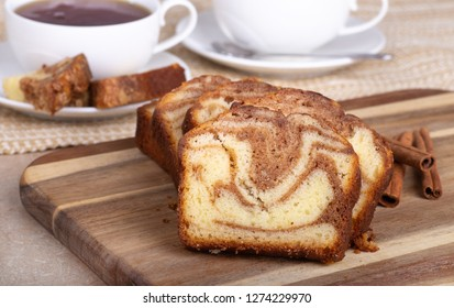 Closeup of a row of sliced cinnamon swirl bread on a cutting board with coffee cups in background