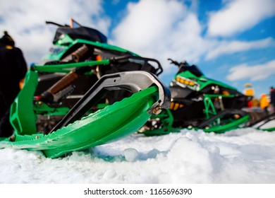 Close-up of row of snowmobiles stand on snow, view from below. Concept of competition, winter sports