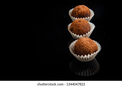closeup row of three healthy useful organic handmade round chocolate candies decorated with brown cocao powder on black mirror background