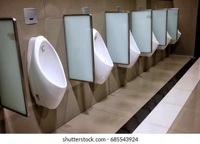 Close-up Row of White Ceramic Urinals in Public Toilet.