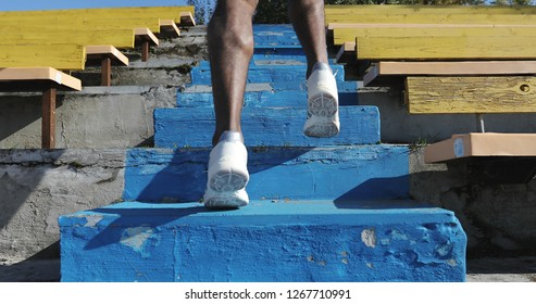 Close-up run up the stairs. Black man trains at the stadium.