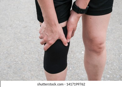 Closeup of runner woman wearing knee support to prevent and reduce knee pain from running. Conceptual of injury from running workout.