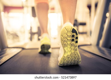 Closeup of running sport shoes at the gym while a young caucasian woman is having jogging on the treadmill