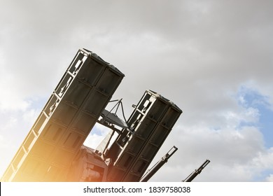 A closeup of a Russian anti-aircraft missile launcher pointing upwards against a blue sky with clouds.
