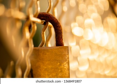 Closeup of a rusted padlock with golden bokeh