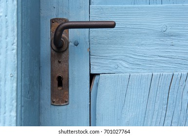 closeup of rustic blue door with old doorhandle