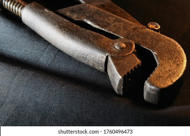 Closeup of a rustic old pipe wrench on black fabric.