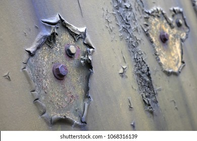 Closeup of rusty bolt heads surrounded by old cracked paint