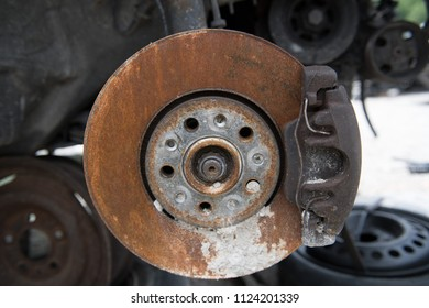 A closeup of a rusty disc brake on a junker car, wheel on the ground in the background