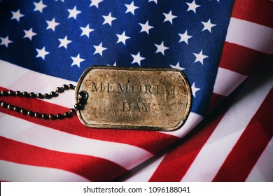 closeup of a rusty dog tag with the text memorial day written in it on a flag of the United States