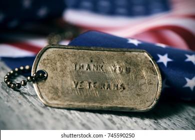 close-up van een roestige hondentag met daarin de tekst bedankveteranen gegraveerd, naast een vlag van de Verenigde Staten, op een rustiek houten oppervlak