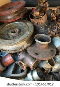 Closeup of rusty machine and plumbing pipes at scrap yard.