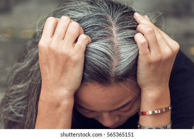 Closeup sad asian young beautiful woman and gray hair with worried stressed face expression looking down