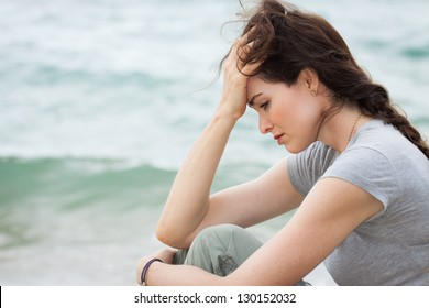 Close-up of a sad and depressed woman deep in thought outdoors.