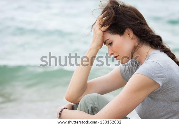 Close-up van een trieste en depressieve vrouw diep in gedachten buiten.