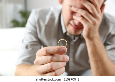 Closeup of a sad husband lamenting after divorce holding the wedding ring in a house interior