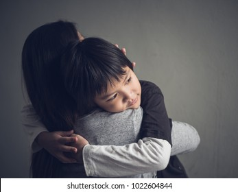 Closeup sad little boy being hugged by his mother at home. Parenthood, Love and togetherness concept.
