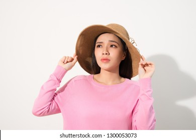 Closeup of sad pensive young woman and straw hat thinking and feeling unhappy over white background