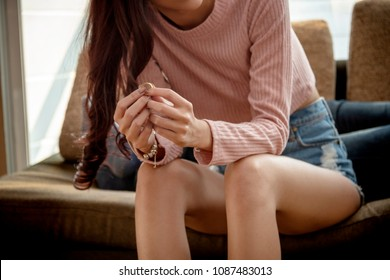 Close-up of a Sad Wife want to Divorce Lamenting Holding the Wedding Ring in a House Interior with Blurred Man on Sofa Background.