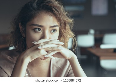 Closeup of sad young Asian woman at cafe covering nose and mouth with clasped hands and staring into vacancy. Upset manager thinking over mistakes. Failure and regret concept