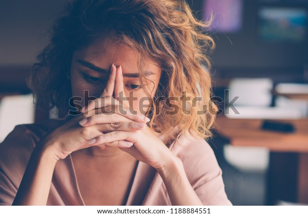 Closeup of sad young Asian woman at cafe leaning head on clasped hands and staring into vacancy. Tired freelancer feeling burnout. Stress and bad news concept