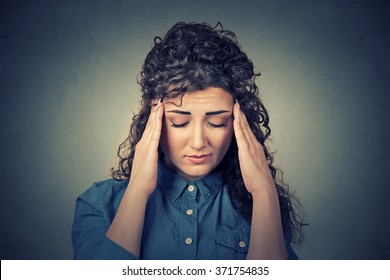 Closeup sad young woman with worried stressed face expression having headache isolated on gray wall background. Human emotions, mental health concept